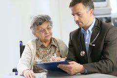 Старшая женщина слушая совет доктора Стоковая Фотография