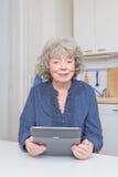 Старшая женщина с eBook Стоковое Фото