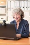 Старшая женщина усмехаясь на веб-камера Стоковые Фотографии RF