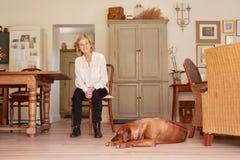 Старшая женщина усмехаясь уверенно в ее доме с собакой Стоковые Изображения RF