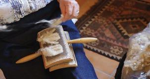 Старшая женщина устанавливая шерстяную пряжу на щетке 4k сток-видео