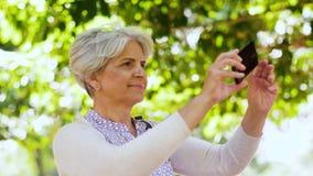 Старшая женщина фотографируя на парке лета акции видеоматериалы