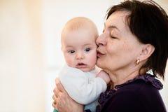 Старшая женщина целует ее внука стоковая фотография rf