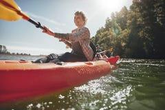 Старшая женщина canoeing в озере на летний день стоковое фото rf