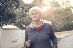 Старшая женщина jogging на улице дороги стоковая фотография
