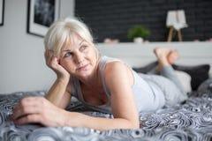 Старшая задумчивая дама лежа на кровати смотря прочь стоковое изображение rf