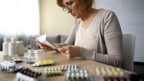 Старшая инструкция чтения дамы, пилюльки blisters лежать на таблице, пожилое заболевание стоковое изображение rf