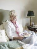 Старшая книга чтения женщины на кровати Стоковые Фото
