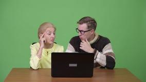 Старшая коммерсантка и молодой красивый человек используя компьтер-книжку совместно акции видеоматериалы