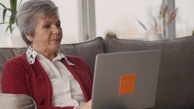 Старшая коммерсантка работая удаленно от дома используя ноутбук видеоматериал