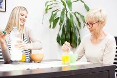 Старшая мать и ее дочь говоря и есть здоровый завтрак хлопьев стоковые фотографии rf