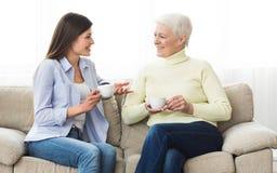 Старшая мать и кофе и говорить дочери выпивая стоковые изображения rf