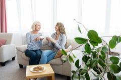 Старшая мать и чай и говорить дочери выпивая стоковое изображение
