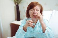Старшая медицина напитка женщины в кровати стоковые изображения rf