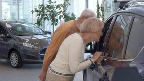 Старшая пара смотрит внутри автомобиля на дилерских полномочиях сток-видео