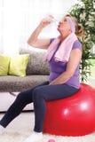 Старшая питьевая вода женщины после тренировать дома Стоковое фото RF