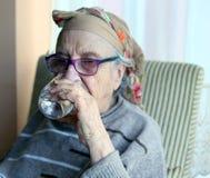 Старшая питьевая вода женщины Стоковые Изображения