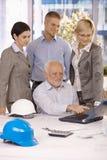 Старшая работа показа архитектора к команде на компьтер-книжке Стоковое Изображение