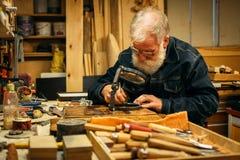 Старшая древесина высекая профессионала во время работы Стоковое фото RF