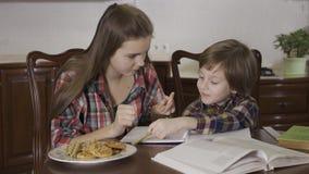 Старшая сестра и младший брат делая домашнюю работу совместно сидя на таблице дома Девочка-подросток помогая немного видеоматериал