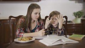 Старшая сестра и младший брат делая домашнюю работу совместно сидя на таблице дома Мальчик неудачно сток-видео