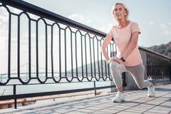 Старшая спортивная женщина протягивая ноги и имея тренировку стоковое изображение