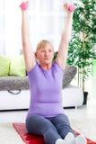 Старшая тренировка женщины с весами дома Стоковые Фото