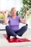 Старшая тренировка женщины с весами дома Стоковая Фотография