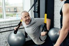 старшая тренировка спортсмена с сопротивлением trx соединяет с тренером Стоковые Фотографии RF