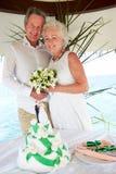 Старшая церемония свадьбы на пляже с тортом в переднем плане Стоковая Фотография RF