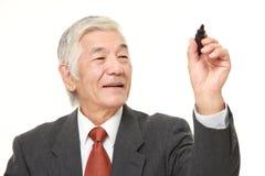 Старшая японская притяжка бизнесмена в воздухе стоковые фото