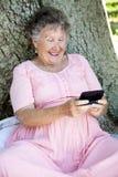 старшая texting женщина Стоковые Изображения