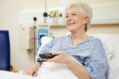 Старшее женское терпеливое смотря ТВ в больничной койке Стоковое Фото