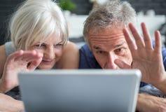 Старшее замужество имея видео- переговор на таблетке стоковая фотография