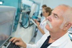 Старшее мужское научное исследование приведения в исполнение исследователя в лаборатории стоковое изображение rf