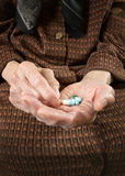 Старшее удерживание женщины сортировало капсулы в ее руках. стоковые изображения