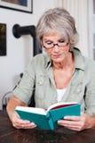 Старшее чтение женщины с стеклами чтения Стоковые Изображения