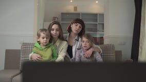 2 старшей сестры с грустными сторонами и более молодые сестра и брат сидя на кресле в ТВ комнаты для гостей и дозора акции видеоматериалы