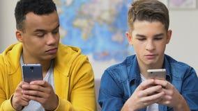 2 старшеклассника просматривая датирующ приложения на смартфонах, выбирая девушек видеоматериал