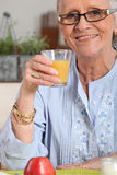 Старше имеющ апельсиновый сок стоковые изображения