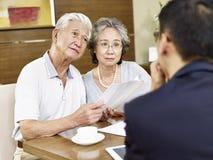 Старшие азиатские пары встречая rep продаж стоковые фотографии rf