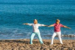 Старшие дамы делая йогу на пляже. Стоковые Фото