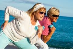 Старшие дамы разрабатывая на пляже. Стоковые Изображения