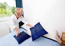 Старшие валики создания женщины на кровати дома Стоковое фото RF