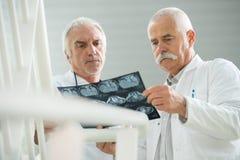 Старшие доктора смотря рентгеновский снимок Стоковые Изображения RF