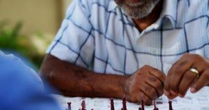 Старшие друзья играя шахмат 4k сток-видео