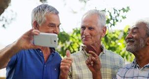 Старшие друзья принимая selfie с мобильным телефоном 4k акции видеоматериалы