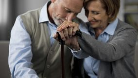 Старшие женатые люди сидя совместно держащ руки на идя ручке, сомкнутость стоковая фотография