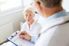 Старшие женщина и доктор с доской сзажимом для бумаги на больнице Стоковое Фото