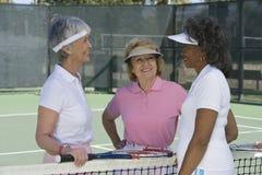 Старшие женщины беседуя на теннисном корте Стоковые Фотографии RF
